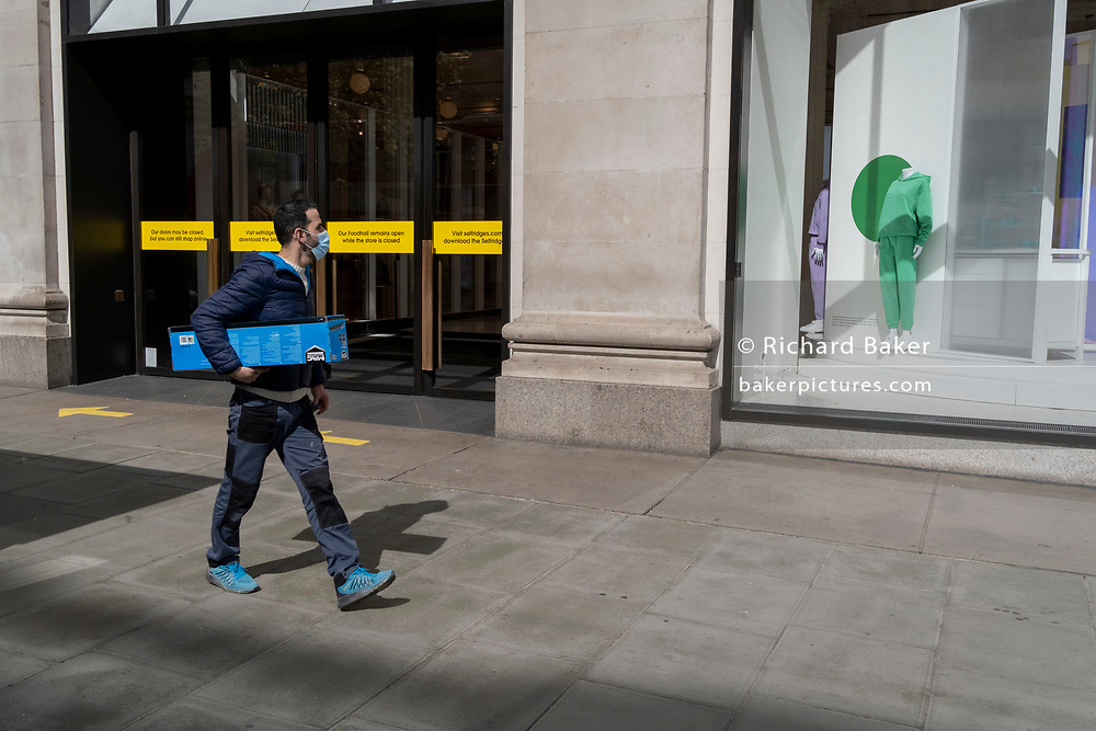 Days before the third Coronavirus lockdown ends, and non-essential retailers and shops re-open again, a shopper walks past the Selfridges department store on Oxford Street, on 9th April 2021, in London, England.