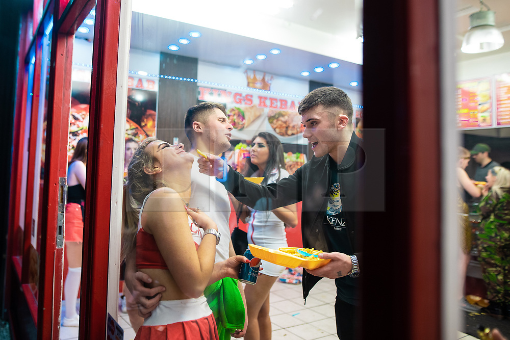 © Licensed to London News Pictures . 27/12/2018. Wigan, UK. A man offers a chip to a woman . Revellers in Wigan enjoy Boxing Day drinks and clubbing in Wigan Wallgate . In recent years a tradition has been established in which people go out wearing fancy-dress costumes on Boxing Day night . Photo credit: Joel Goodman/LNP