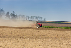 2020 era farmers agriculture tractor pulling a field working implement or planter