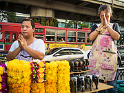21 AUGUST 2015 - BANGKOK, THAILAND:  Flower garland vendors at Erawan Shrine pray during a religious ceremony to honor the dead at the shrine. The Bangkok Metropolitan Administration (BMA) held a religious ceremony Friday for the Ratchaprasong bomb victims. The ceremony started with a Brahmin blessing at Erawan Shrine, which was the target of a bombing Monday night. After the blessing people went across the street to the plaza in front of Central World mall for an interfaith religious service. Theravada Buddhists, Mahayana Buddhists, Muslims, Sikhs, Hindus, and Christians participated in the service. Life at the shrine, one of the busiest in Bangkok, is returning to normal. Friday the dancers and musicians who perform at the shrine resumed their schedules.      PHOTO BY JACK KURTZ