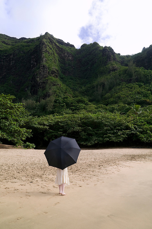 A woman walks along the sand with a large umbrella on Kee Beach, Kauai, Hawaii with the lush mountains in the background