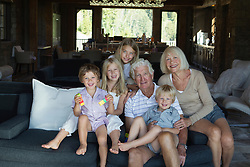 grandparents with their four grandchildren gathered together on a couch for a family photograph at home