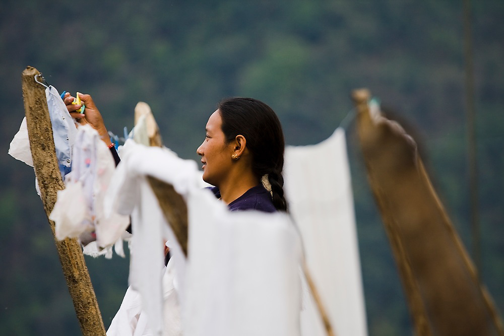 A woman hangs clothes to dry outside her home in Chhomrong, Annapurna Himalaya, Nepal.