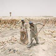 Brick makers fill up a bag from sand in 52 degrees heat.