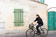 Man riding bicycle past wooden shutters in Les Portes en Re, Ile de Re, France