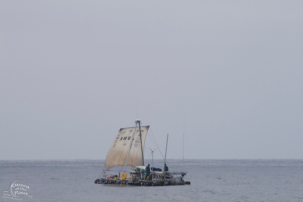 """On the second day of the voyage, the """"Junk"""" raises it sails for a brief time. On Sunday June 1, the raft named """"Junk""""  left Long Beach for it's 2100 mile voyage to Hawaii to bring attention to the plastic marine debris (nicknamed the plastic soup) accumulating in the North Pacific Gyre. The raft was designed and will be sailed by Dr. Marcus Eriksen of the Algalita Marine Research Foundation, and Joel Paschal, it is constructed from 15,000 plastic bottles, an airplane fuselage, discarded fishing nets and a solar generator. The raft was towed for two and a half days to near San Nicholas Island, about 65 mile of the coast of California, so it could catch favorable winds for it's trip. The tow boat was the ORV Alguita, captained by Charlie Moore of the Algalita Marine Research Foundation, the man credited for first discovering the plastic soup in the Gyre over 12 years ago."""