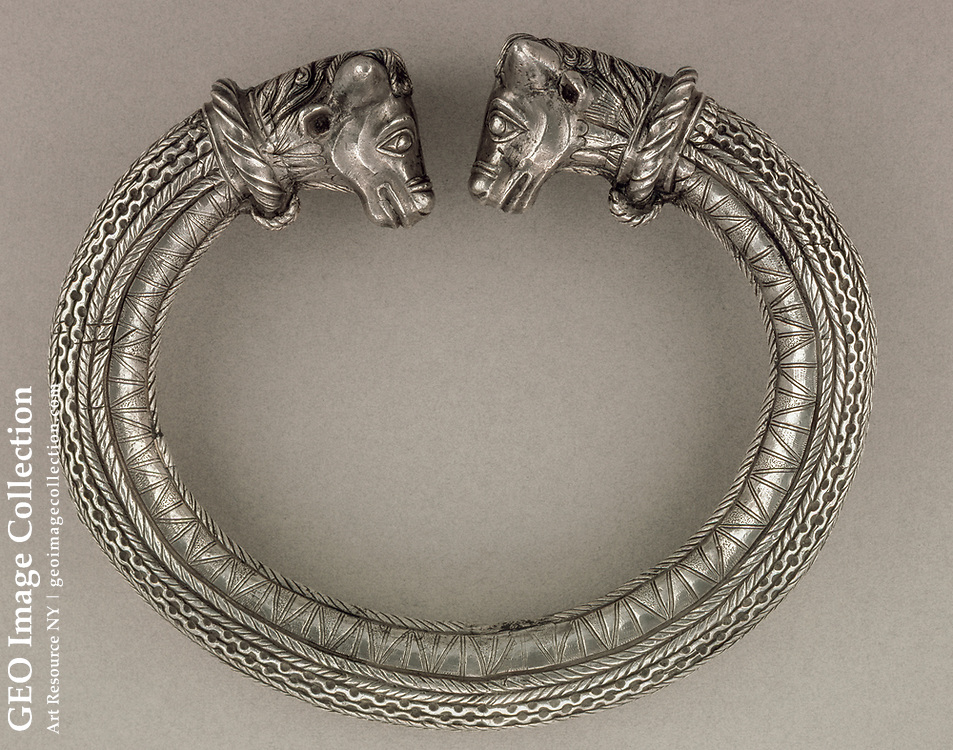 A Celtic torque is decorated with a two bull heads.