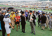 Crowds of spectactors in traditional top hats and tails in members enclosure at Epsom Racecourse for Derby Day, UK