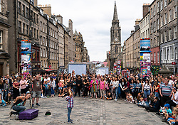 Edinburgh, Scotland, UK; 5 August, 2018. Edinburgh Fringe Festival's first weekend sees thousands of tourists and locals on the Royal Mile  enjoying the free street performers. Pictured; Audience watching street performance.