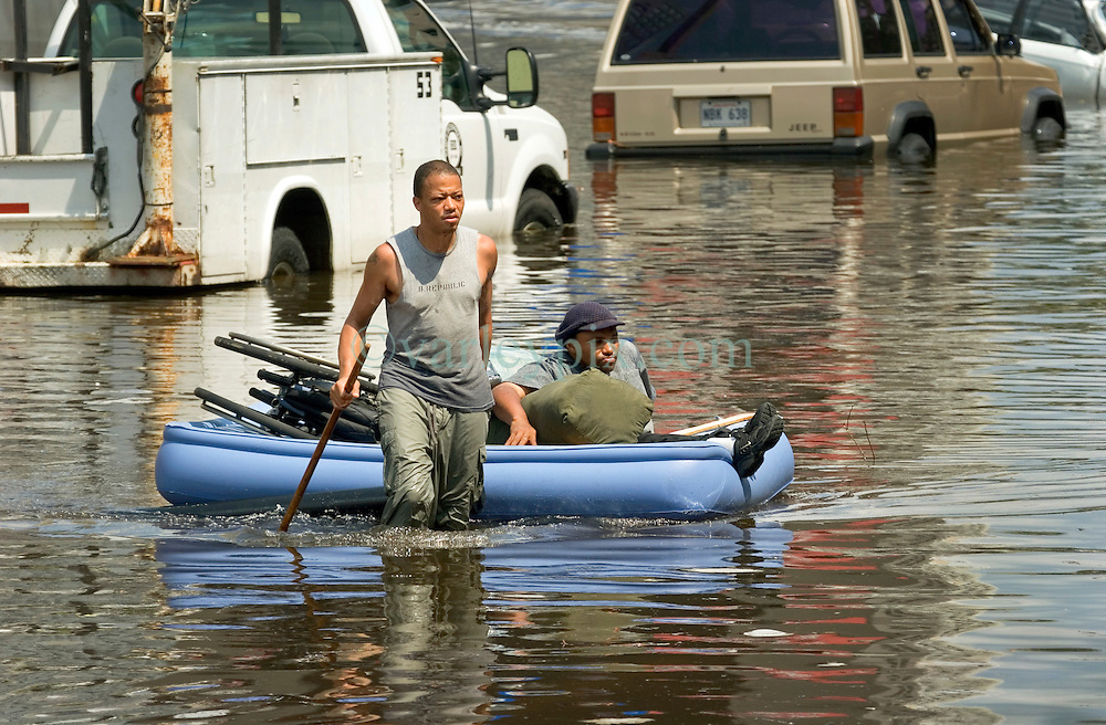 30 August, 2005. New Orleans Louisiana. Hurricane Katrina aftermath. <br /> An evacuee from the storm pulls his disabled friend through the flood waters on an inflatable bed to the Superdome.<br /> Photo Credit: Charlie Varley/varleypix.com