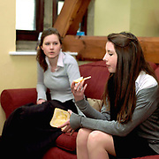 Teenage girls eating toast in the common room at Ampleforth College, North Yorkshire, UK. Ampleforth College is a coeducational independent day and boarding school in the village of Ampleforth, North Yorkshire, England. It opened in 1802 as a boys' school, and is run by the Benedictine monks and lay staff of Ampleforth Abbey.