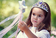 Young girl in princess costume with magic wand.