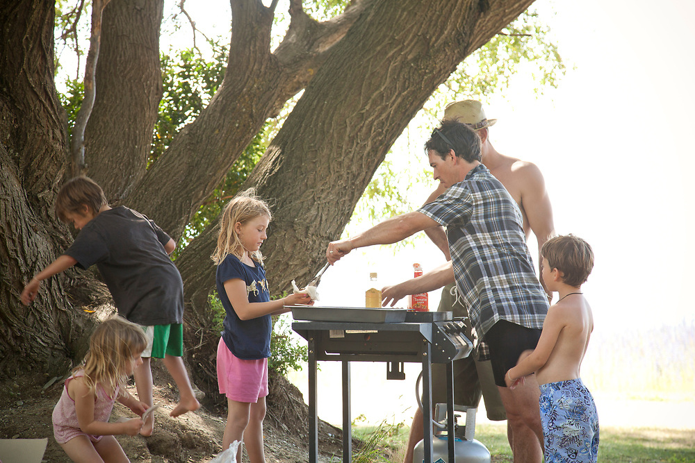 Dads cooking on barbeque with children gathered around