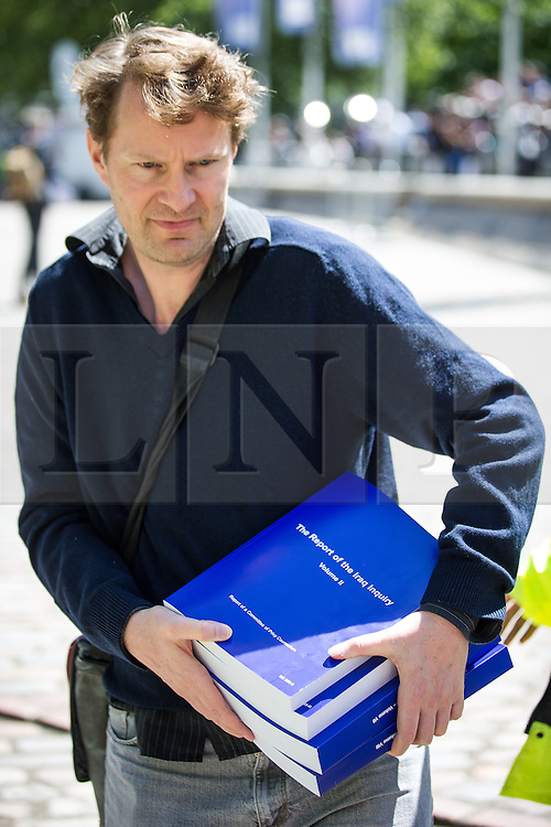 © Licensed to London News Pictures . 06/07/2016 . London , UK . First copies of the report being carried away from the venue . Scene outside the Queen Elizabeth II Conference Centre in Westminster , ahead of the publication of the Chilcot Inquiry's report in to the 2003 invasion of Iraq . Photo credit : Joel Goodman/LNP