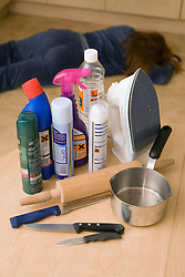 Woman lying on the floor; a selection of household products used for domestic abuse on the table,