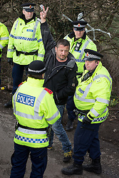 © Licensed to London News Pictures . 21/03/2014 . Barton Moss , Manchester , UK . Police detain one of the men , having cut him free . Two men lock themselves together using concrete and metal pipes and lie in the middle of the road down which lorries from the iGas site need to pass . The Barton Moss anti-fracking demonstration camp today (Friday 21st March 2014) . Photo credit : Joel Goodman/LNP