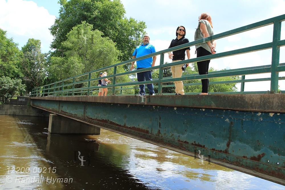 Hyfi CEO Brandon Wong talks with City Manager Joe Sawyer and Parks & Recreation Director Lisa Champion-Julian on Shiawassee River bridge before installing water-level sensor; Corunna, Michigan.