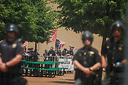 Police guard members of the KKK who are holding a rally. Members of the KKK arrive after a police escort. Hundreds of counter protesters, including the Nation of Islam, New Black Panthers, and Huey Newton Gun Club, American Indian Movement, and ANTIFA gathered in downtown Dayton, Ohio to protest members of the Honorable Sacred Knights - a Ku Klux Klan group from Indiana. There were no arrests, and the protests ended peacefully as hundreds of police worked to keep the event peaceful and the protesters separated. Much of downtown Dayton was shutdown, and the courthouse square, where the KKK gathered, was surrounded by fence. Members of the KKK were given a police escort to the site, where about a dozen of them gathered, and then a police escort to safety.