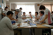 Nurses and Doctors surround the table for their morning conference to check every patients' condition. Aiwa Hospice holds 40 stage-4 cancer patients with 6 doctors and 25 nurses. On November 19th, 2019 at Aiwa Hospice in Nagano, Japan.