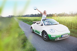 Happy couple driving in a car Beetle Cabrio woman waving with hat, Bavaria, Germany
