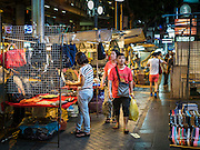 26 MAY 2016 - BANGKOK, THAILAND: Tourists walk through the Silom Road night market. The night market on Silom Road, close to Bangkok's famous Patpong tourist area, is being closed by the Bangkok municipal government. Vendors have been told they have to leave the sidewalk on Silom Road by the end of May, 2016. The market is the latest street market being shut down by city officials as a part of the government's plan to clean up Bangkok. The Silom Road night market sells mostly tourist oriented clothes, inexpensive Thai art, and bootleg movies on DVD.       PHOTO BY JACK KURTZ