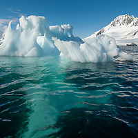 A weathered iceberg drifts in the Neumayer Channel near the Antarctic Peninsula, Antarctica. The National Geographic Endeavor is anchored in the background, adjacent to Wiencke Island.  Anvers Island is on the left.
