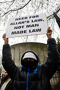 An Islamic extremist protests opposite the London Libyan embassy and demand Shariah law after the Gaddafi uprising. Holding up his placards that ask for Allah's Holy law and a Shariah way of life for Libya and that Democracy is the path to Hellfire, the young British radical stands behind barriers near Hyde Park Corner denouncing Colonel Gaddafi and for their views and ideology to become the norm for the north African country.