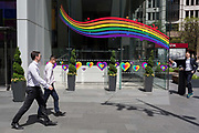 At lunchtime, businessmen in their shirts walk past a window featuring a rainbow and hearts for the Insurance brand Aviva in the City of London, the capitals financial district, on 17th June 2019, in London, England.