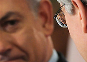 Israeli Prime Minister Benjamin Netanyahu is magnified in the glasses of Prime Minister Stephen Harper as they  hold a joint press conference following their meeting on Parliament Hill in Ottawa on Friday, March 2, 2012. THE CANADIAN PRESS/Sean Kilpatrick