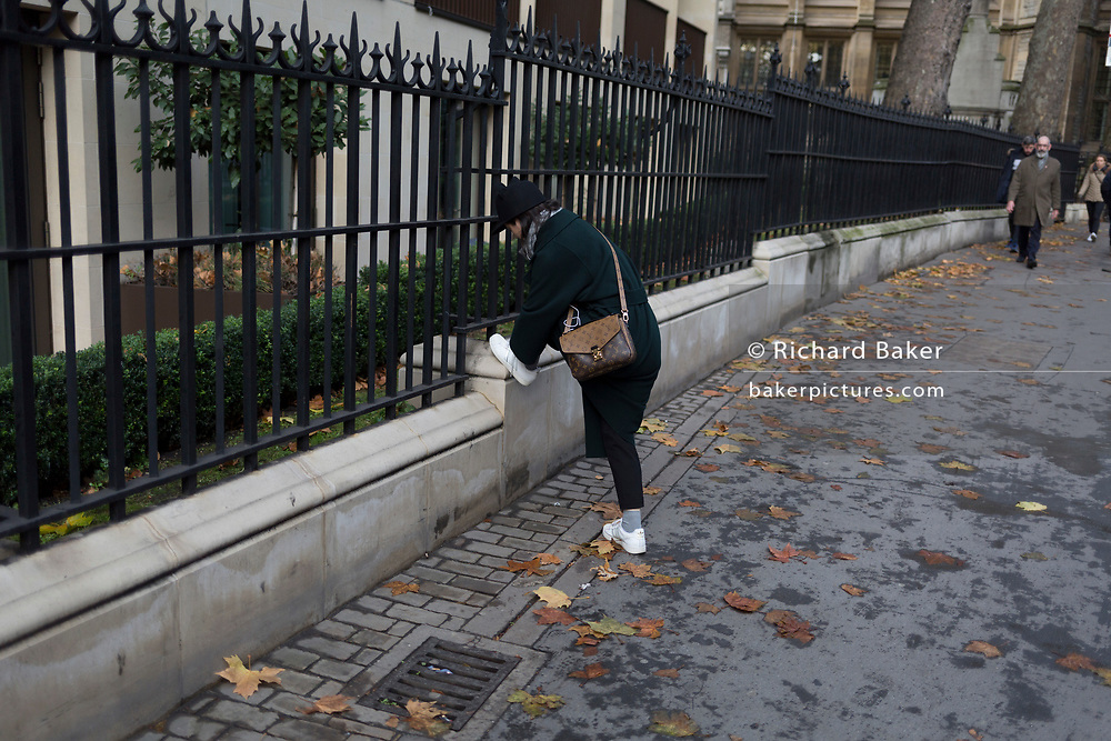 A lady stoops to tie loose laces on her trainers, in New Fetter Lane, on 27th November 2017, in the City of London, England.
