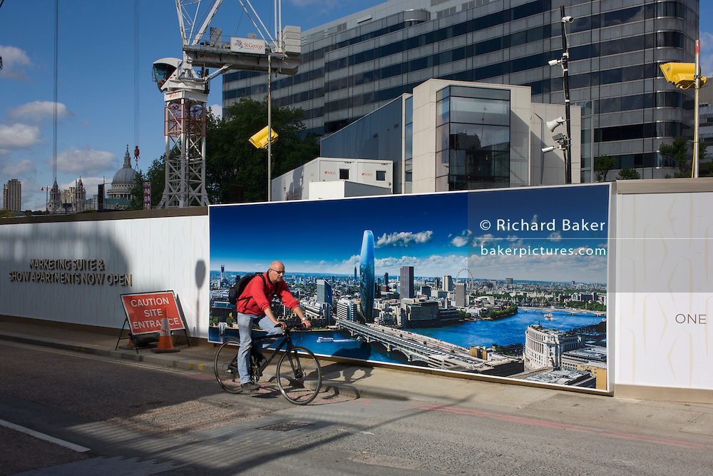 A cyclist passes a large construction hoarding that shows 1, Blackfriars, a property development marketing suite hoarding landscape. 1 Blackfriars or One Blackfriars, will be a mixed-use development approved for construction at the junction of Blackfriars Road and Stamford Street at Bankside, London. The development make make up a 52-storey tower of a maximum height of 170m and two smaller buildings of 6 and 4 stories respectively. Uses include residential flats, a hotel and retail. In addition a new public space will be created.