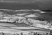 Dramatic rain clouds hover over the patchwork fields of Abney Low with Higger Tor in the distance. Captured from Bretton Clough. Spring in the Peak District National Park, Derbyshire. May, England, UK. Infrared capture with black and white conversion.