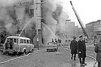 Firemen tackle blaze following Provisional IRA 500 lb bomb attack on the RUC police station, Musgrave Street, Belfast, N Ireland. Adjacent buildings seemed to have suffered more damage than the actual police station. It was claimed the bomb attack was in retaliation for the death of IRA member Hugh Coney who was shot dead by a sentry during an escape attempt at the Maze Prison. Twenty nine other prisoners were captured within a few yards of the prison, and the remaining three were back in custody within 24 hours. 1974110604c.<br />