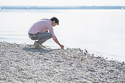 Young man gathering stones beach water