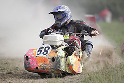 © Licensed to London News Pictures. 24/09/2016. Five Oaks, UK. A competitor rides through the dust as he takes part in a race at the Lawn Mower Racing World Championships. A weekend long set of races using specially adapted lawn mowers will see a World Champion announced on Sunday. Photo credit: Peter Macdiarmid/LNP