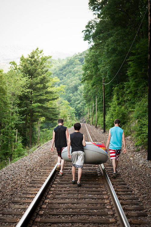 Unicoi County, Tennessee - May 25, 2015: On Memorial Day, boys carry a small raft up the railroad tracks that parallel the Nolichucky River, hiking to an entry point on the river.