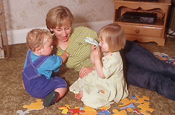 Mother lying on living room floor playing with young daughter and son,