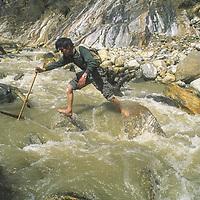 TIBET, Tsangpo Gorge, Trekker fords rain-swollen side stream from Namcha Barwa Glacier Himalaya
