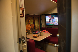 """A movie plays in the train car room of Maria Maltsevam, a rider with The Thundering Cossack Warriors. Ringling Bros. and Barnum & Bailey Circus started in 1919 when the circus created by James Anthony Bailey and P. T. Barnum merged with the Ringling Brothers Circus. Currently, the circus maintains two circus train-based shows, the Blue Tour and the Red Tour, as well as the truck-based Gold Tour. Each train is a mile long with roughly 60 cars: 40 passenger cars and 20 freight. Each train presents a different """"edition"""" of the show, using a numbering scheme that dates back to circus origins in 1871 — the first year of P.T. Barnum's show."""