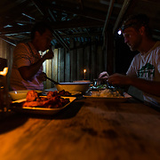 Andrew Whiteford, Jay Goodrich, Mr. Sak, and Win Jalawin eat dinner in local tribe member's house in the higher altitude jungle near Ban Sop Gai, Thailand.