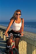 Woman relaxes next to ocean during bike ride, Butterfly Beach, Santa Barbara, California
