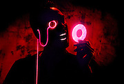 Silhouette of a man with a glowing monacle  holding a glowing ring.Black light