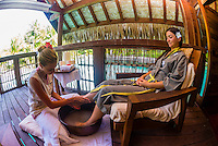 A woman getting a foot massage on the  outdoor terrace of the Kahaia spa suite at the Spa in the Four Seasons Resort Bora Bora, French Polynesia.