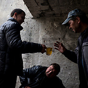 People displaced by the war share a cup of tea at the entrance to a bomb shelter in Petrovskiy district, Donetsk.
