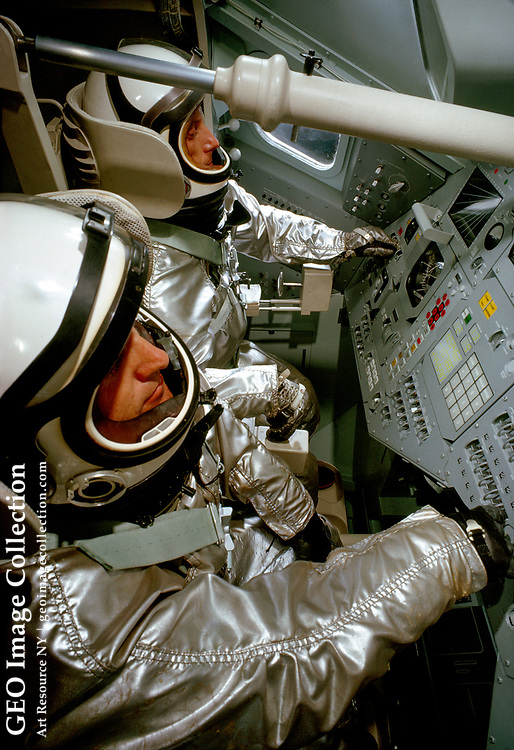 Two pressure-suited test subjects stand in front of a mock-up Apollo command module.