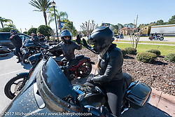 Mandy Campbell Rossmeyer high fives Karen Davidson as they arrive at Destination Daytona after the Harley-Davidson Women's Ride for MDA during Daytona Bike Week. Daytona Beach, FL. USA. Thursday March 16, 2017. Photography ©2017 Michael Lichter.