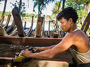 06 NOVEMBER 2014 - SITTWE, RAKHINE, MYANMAR: A Rohingya Muslim carpenter works on planks that will be used to build a new boat (background) near an IDP camp a few miles from Sittwe, Myanmar. The government of Myanmar has forced more than 140,000 Rohingya Muslims who used to live in Sittwe, Myanmar, into squalid Internal Displaced Person (IDP) camps around Sittwe. The forced relocation took place in 2012 after sectarian violence devastated Rohingya communities in Sittwe and left hundreds dead. None of the camps have electricity and some have been denied access to regular rations for nine months. Conditions for the Rohingya in the camps have fueled an exodus of Rohingya refugees to Malaysia and Thailand. Tens of thousands have put to sea in rickety boats hoping to land in Malaysia but sometimes landing in Thailand. The exodus has fueled the boat building boom on the waterfront near the camps. Authorities expect the pace of refugees fleeing Myanmar to accelerate during the cool season, December through February, when there are fewer storms in the Andaman Sea and Bay of Bengal.   PHOTO BY JACK KURTZ