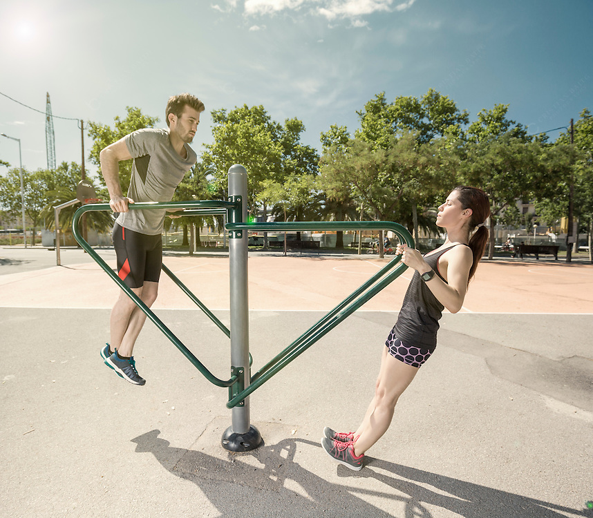 young man and woman doing exercises in a city park