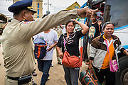 16 JUNE 2014 - POIPET, CAMBODIA: A Cambodian police officer tells returning Cambodian migrants how to get back to their home villages after the migrants returned to Cambodia Monday. More than 150,000 Cambodian migrant workers and their families have left Thailand since June 12. The exodus started when rumors circulated in the Cambodian migrant community that the Thai junta was going to crack down on undocumented workers. About 40,000 Cambodians were expected to return to Cambodia today. The mass exodus has stressed resources on both sides of the Thai/Cambodian border. The Cambodian town of Poipet has been over run with returning migrants. On the Thai side, in Aranyaprathet, the bus and train station has been flooded with Cambodians taking all of their possessions back to Cambodia.  PHOTO BY JACK KURTZ
