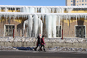 ALTAY, CHINA - JANUARY 12: (CHINA OUT) <br /> <br /> A citizen passes by a residential building where icefalls hang all over as the snow melts on daytime and freezes at night on January 12, 2016 in Altay Prefecture, Xinjiang Uyghur Autonomous Region of China. Affected by El Nino Phenomenon, Altay Prefecture seems to be a warm winter this year compared with previous winters.<br /> ©Exclusivepix Media